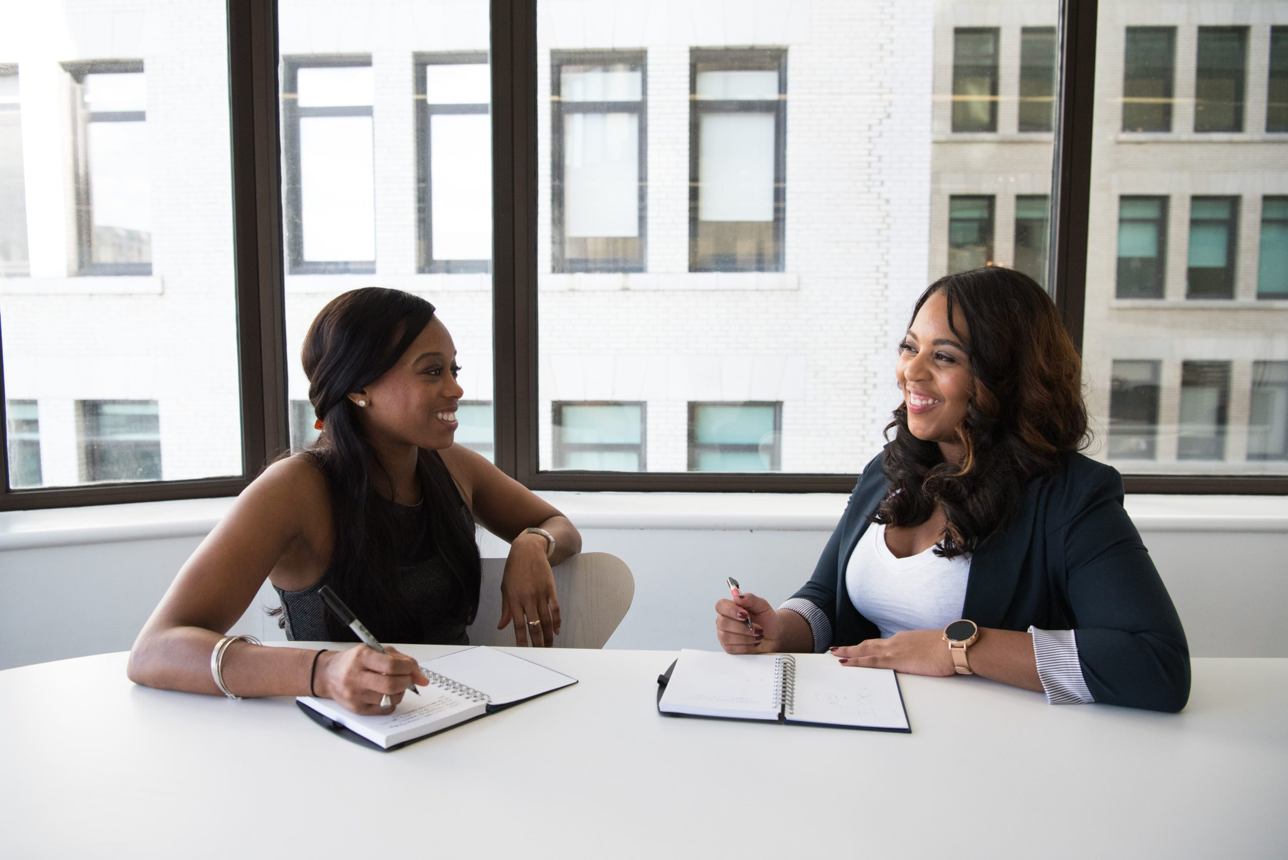 Two women of color sitting at a table working