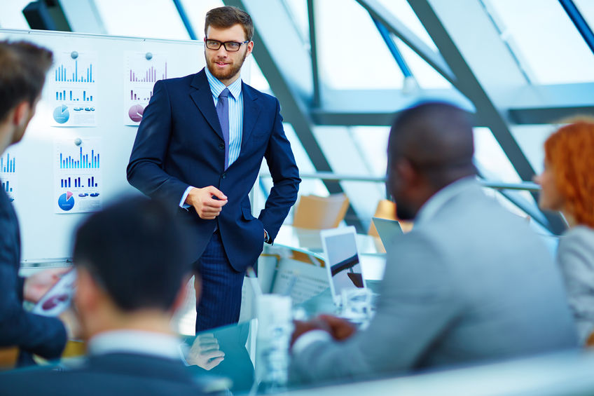 Business man talking to group of team members in conference room