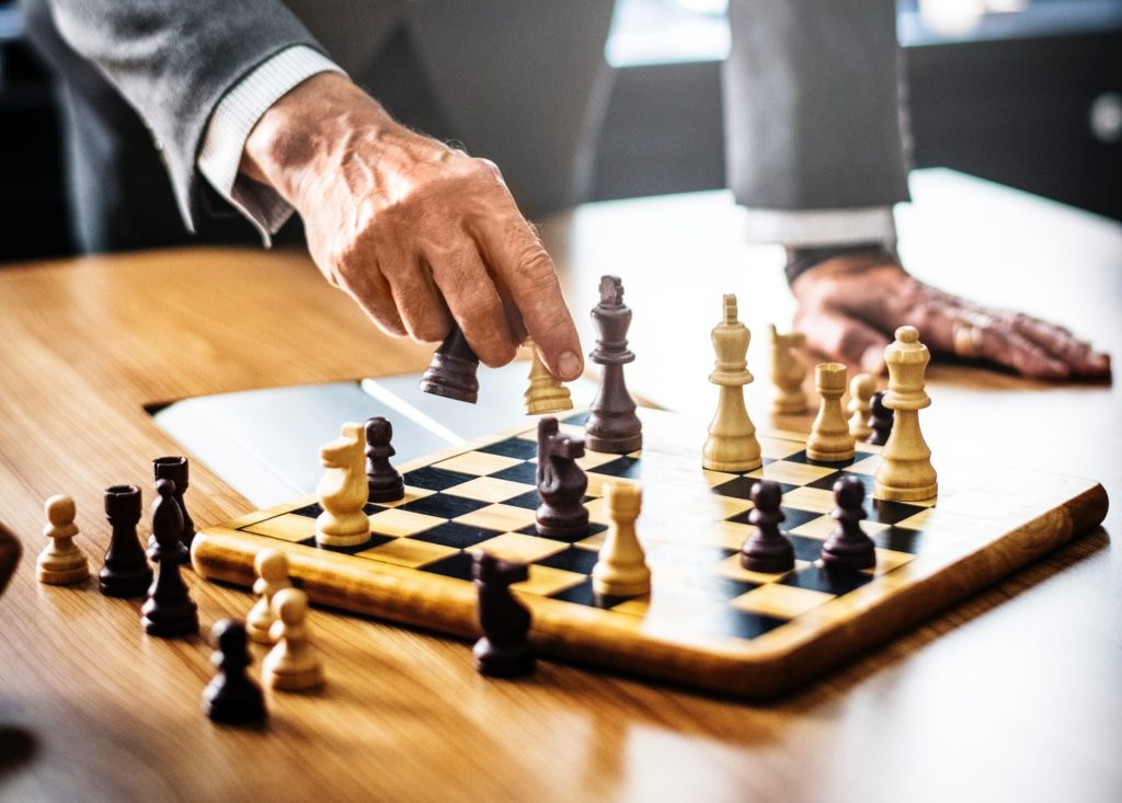 Man standing and playing chess