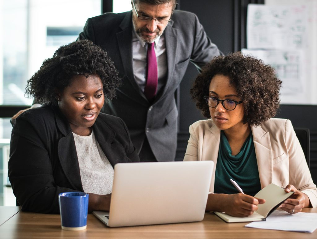 Man looking over shoulders of two women in the office