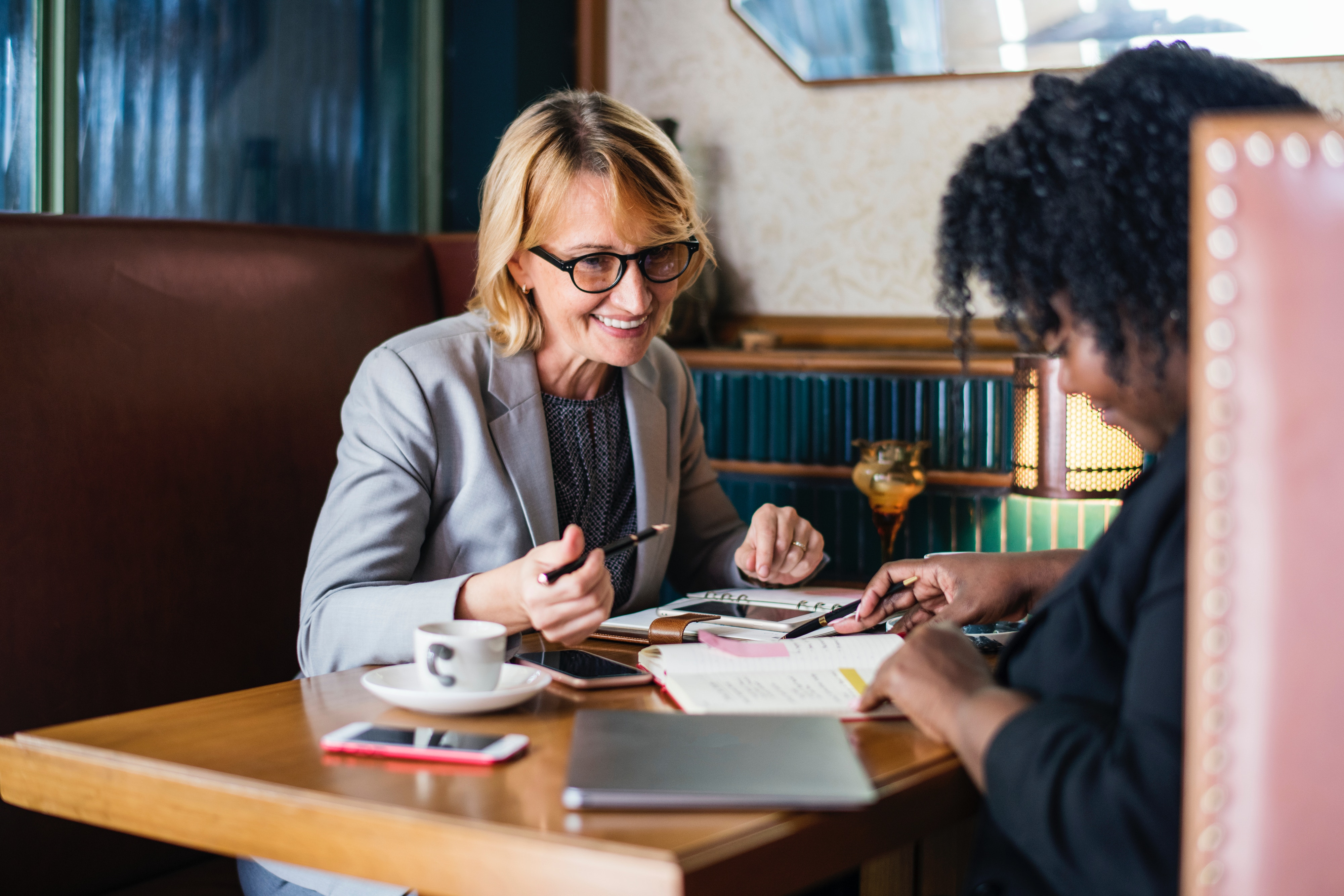 Woman mentoring woman over coffee