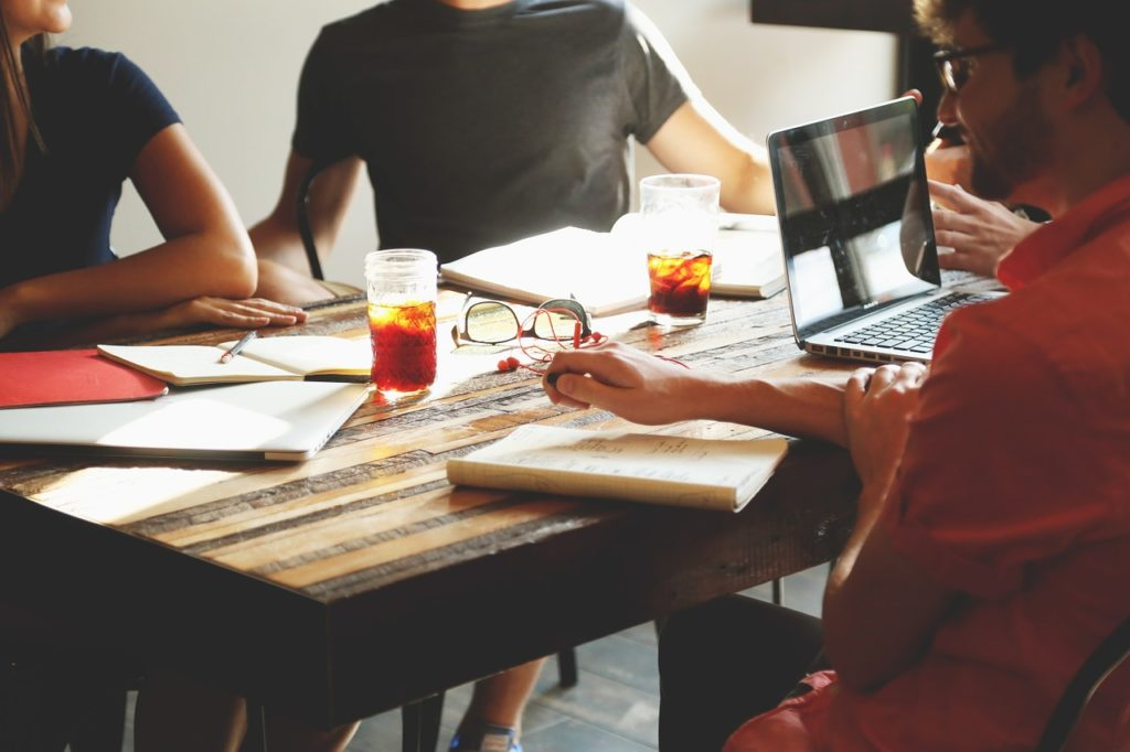 Employees sitting around table preparing strategic plan drinking coffee