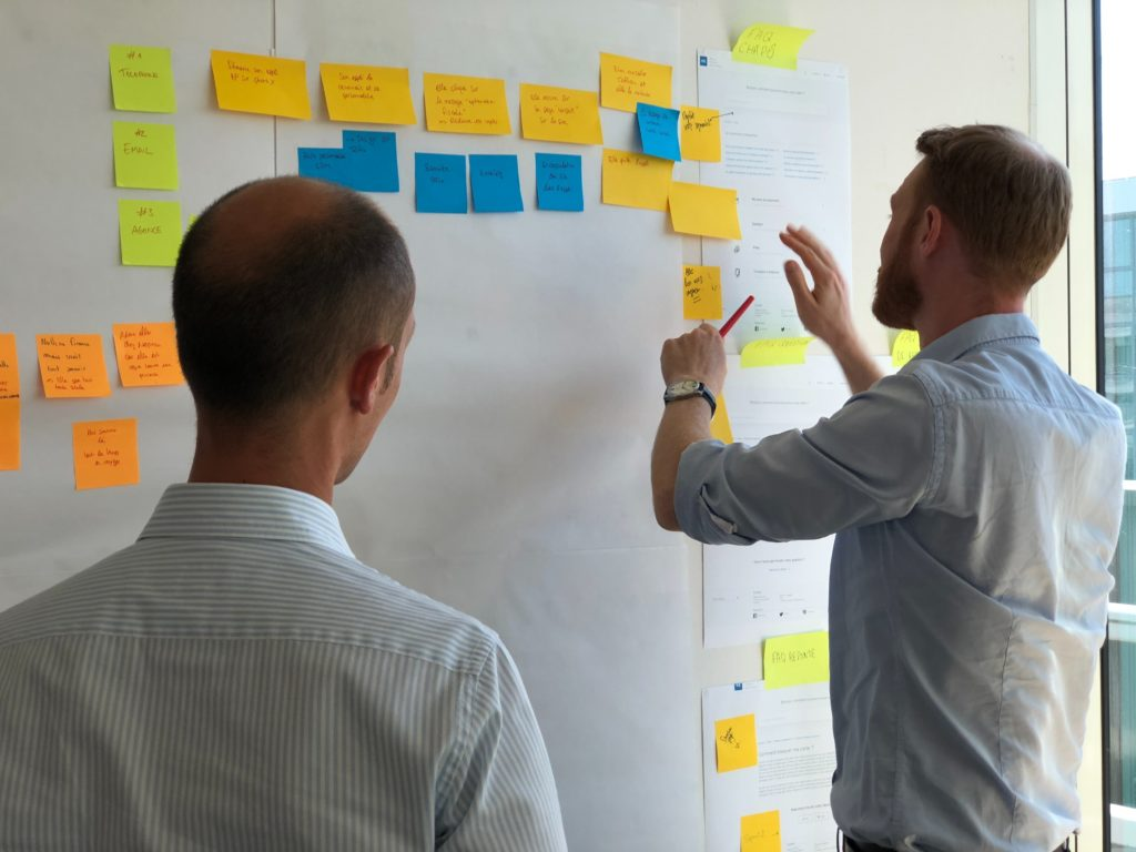 Leader mid-career assisting employee with work post-it notes on board