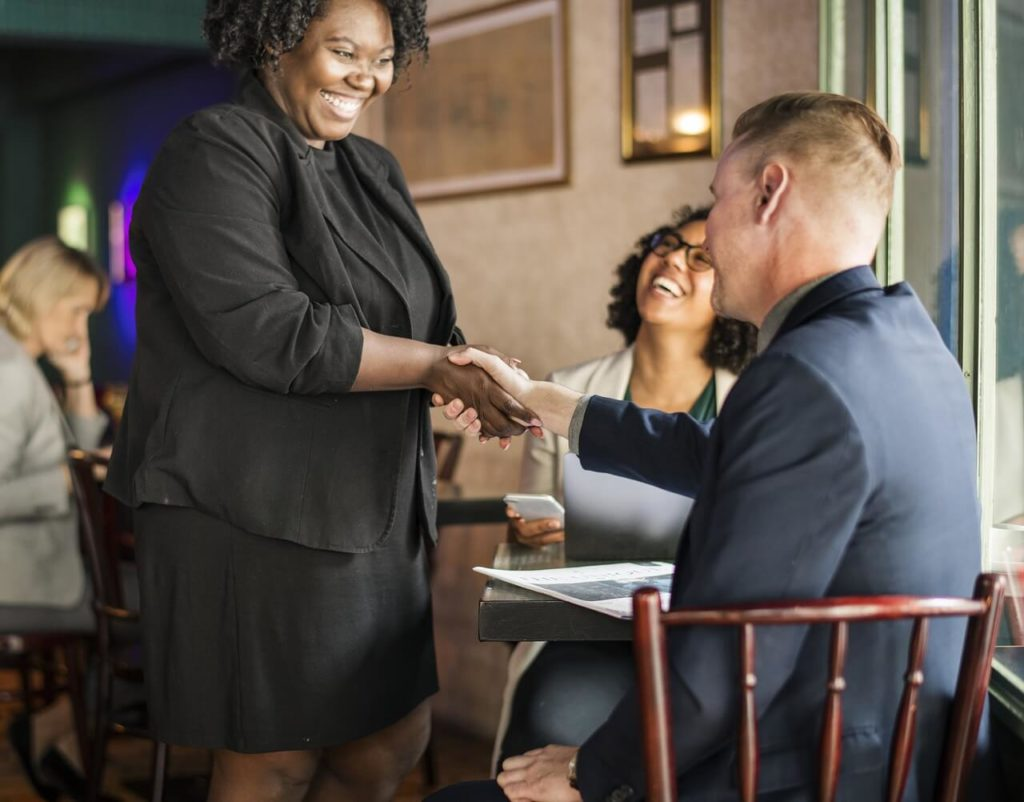 African-american woman leader meeting new employee at cafe