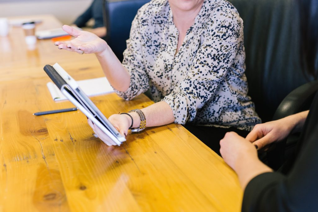 Woman leader with tablet mid-career talking to employee