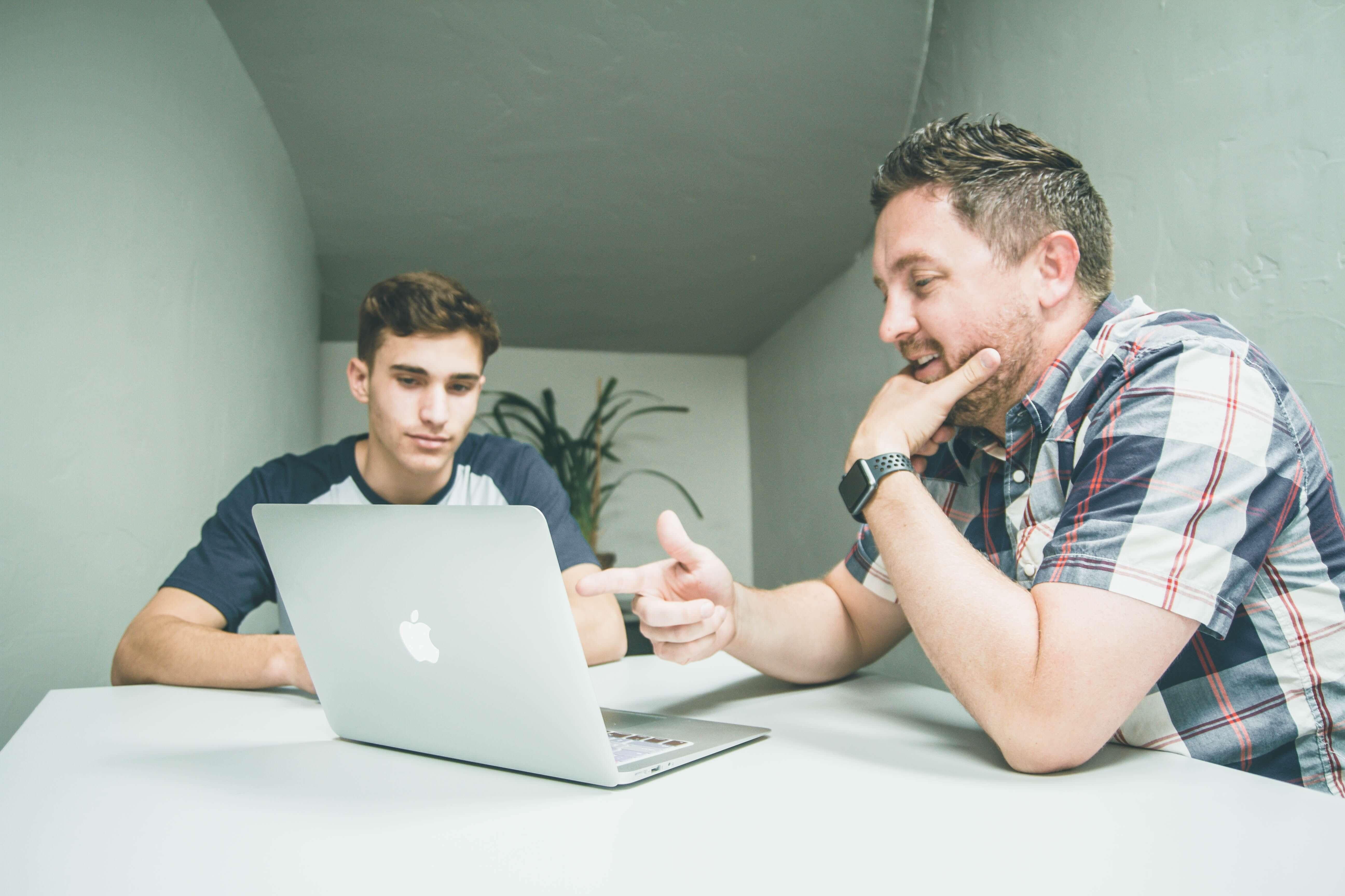 two men sitting around a macbook