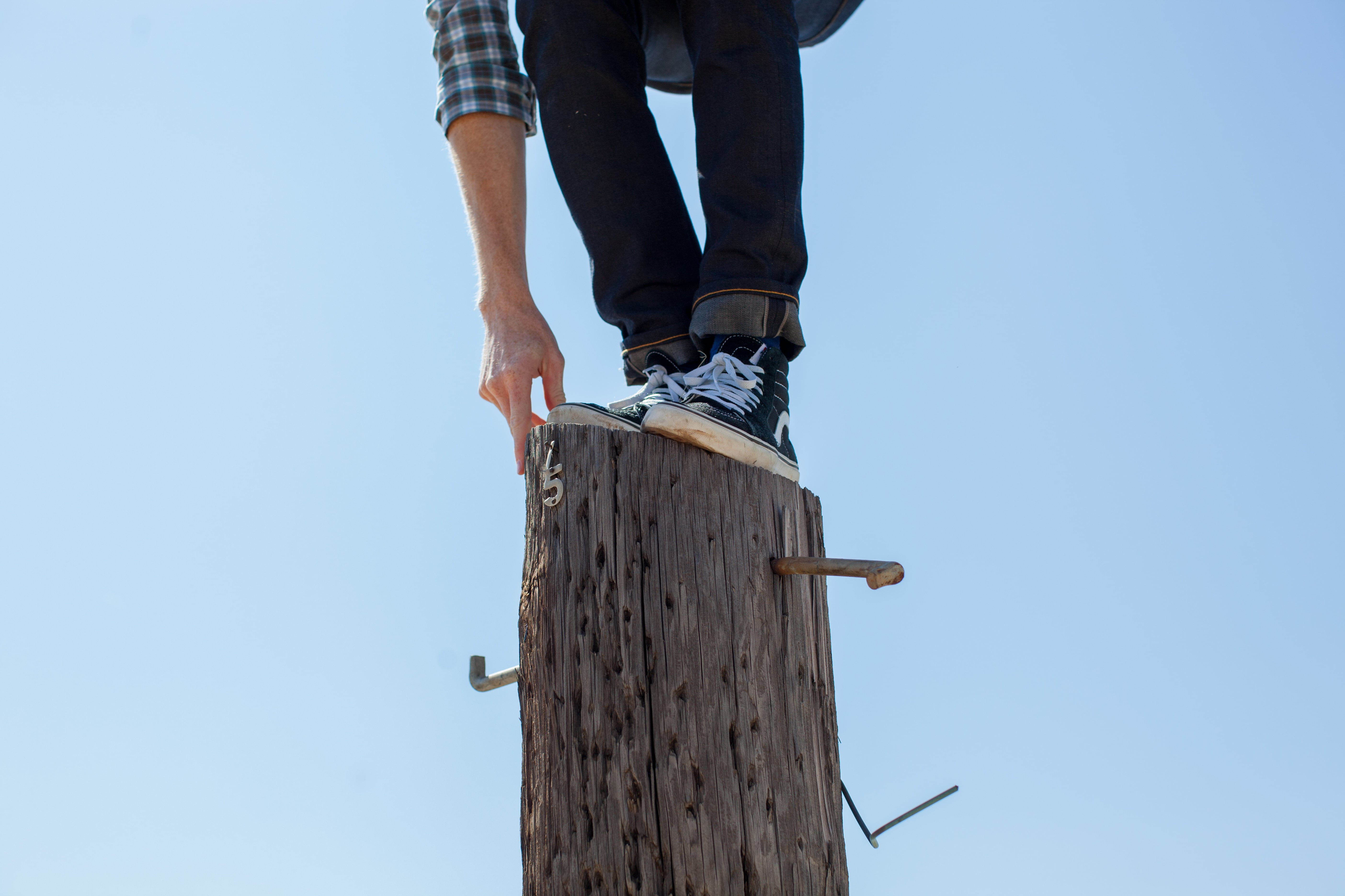 Man standing on high pole