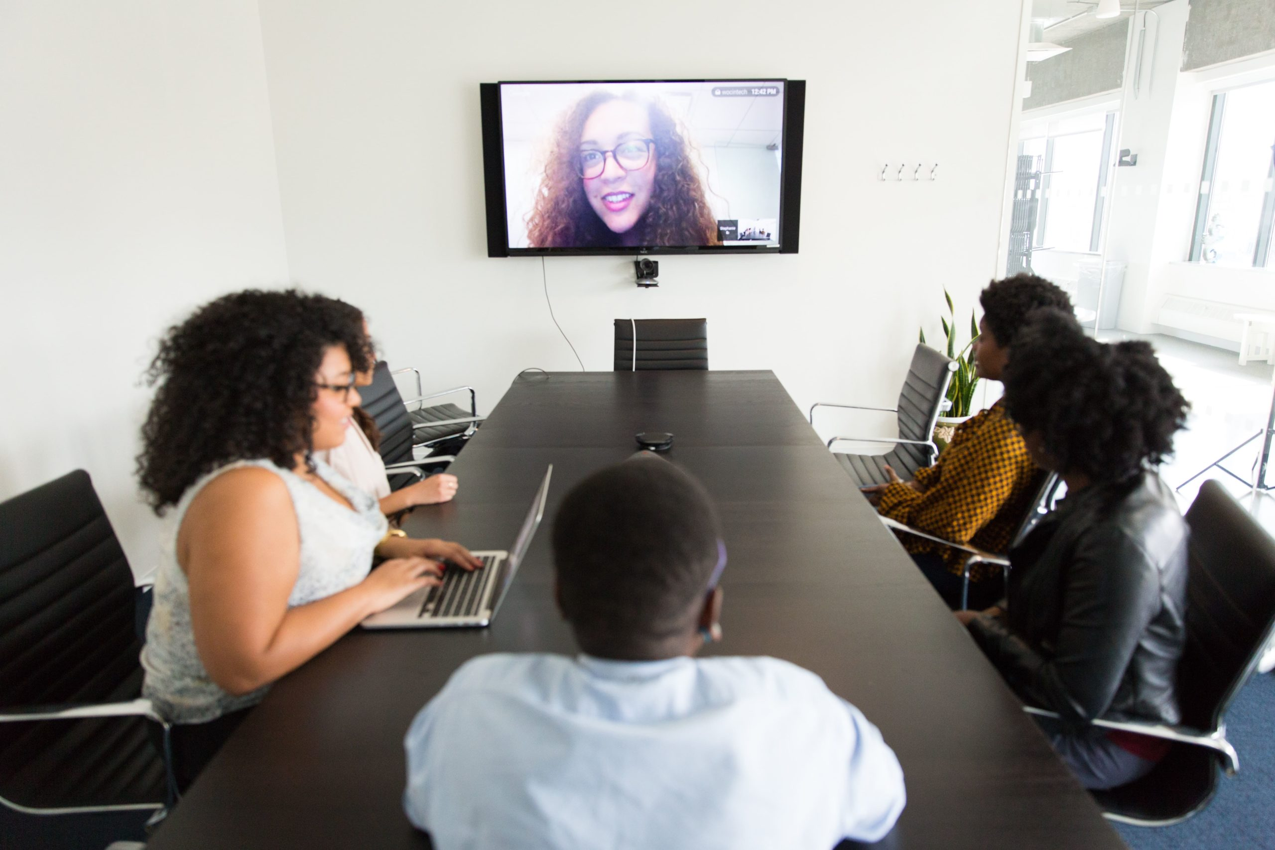 women-sitting-conference-table-videoconference-flatscreen-television