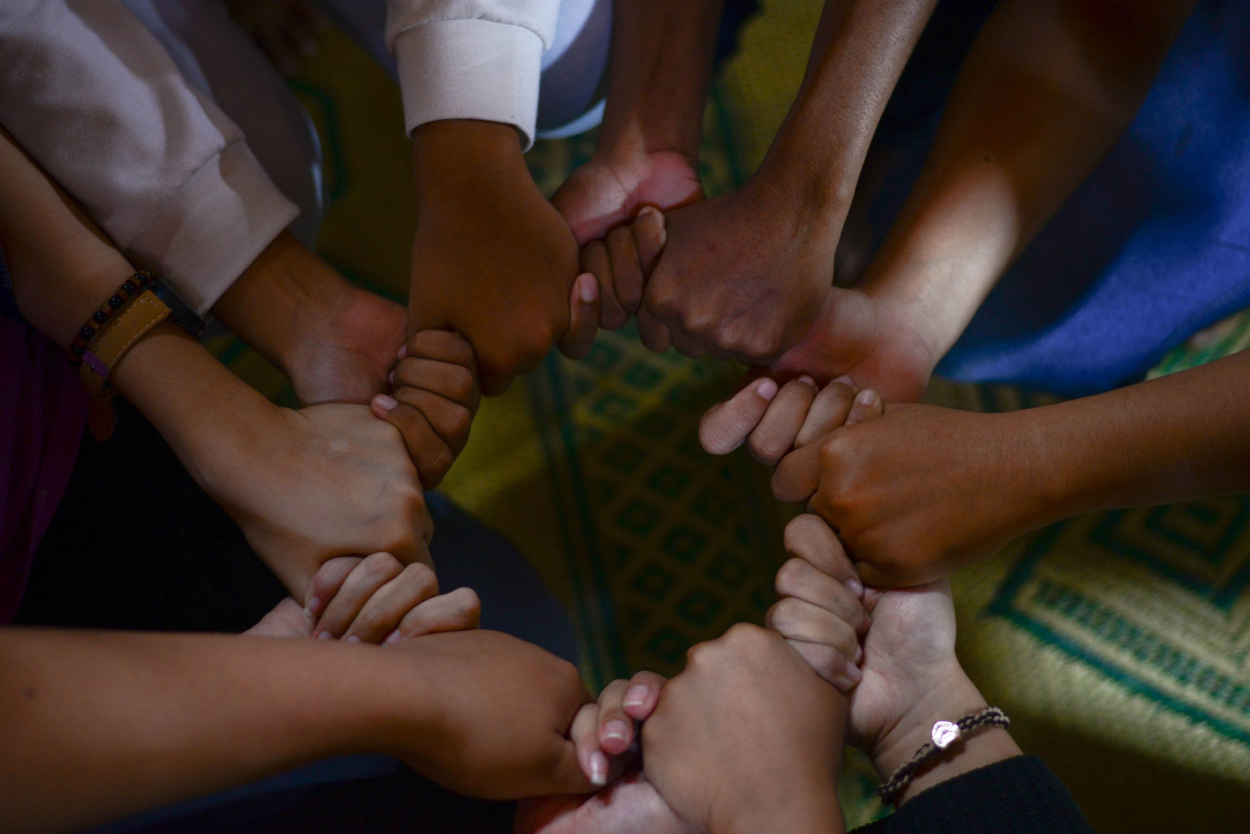 group of different colored hands holding one another in harmony