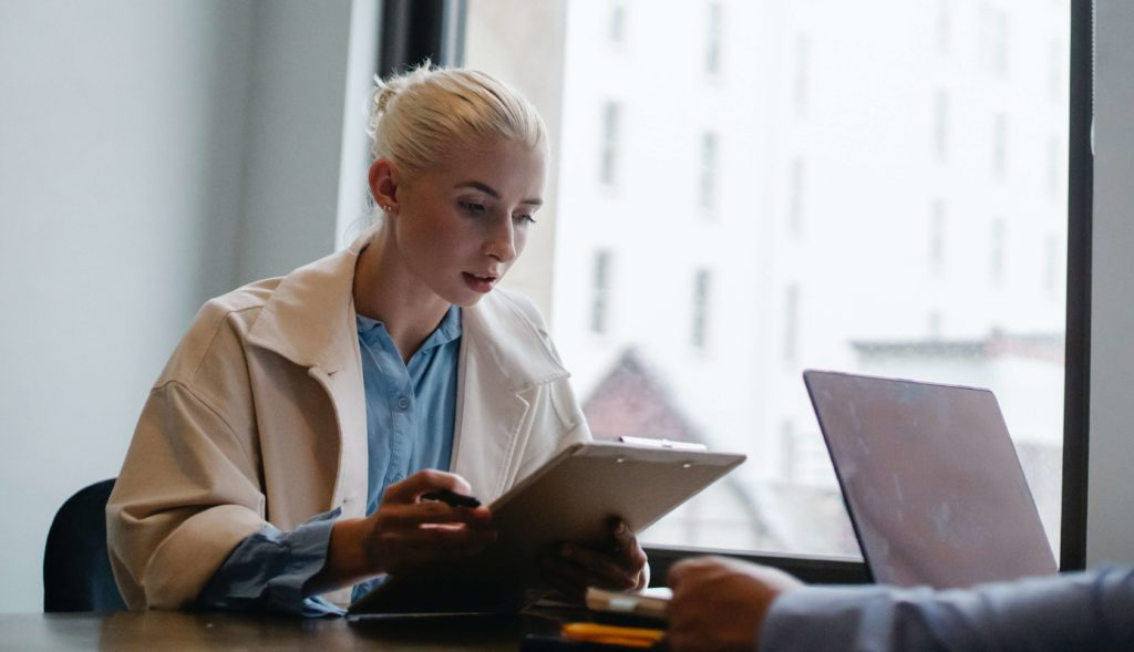 White woman looking at clipboard in office