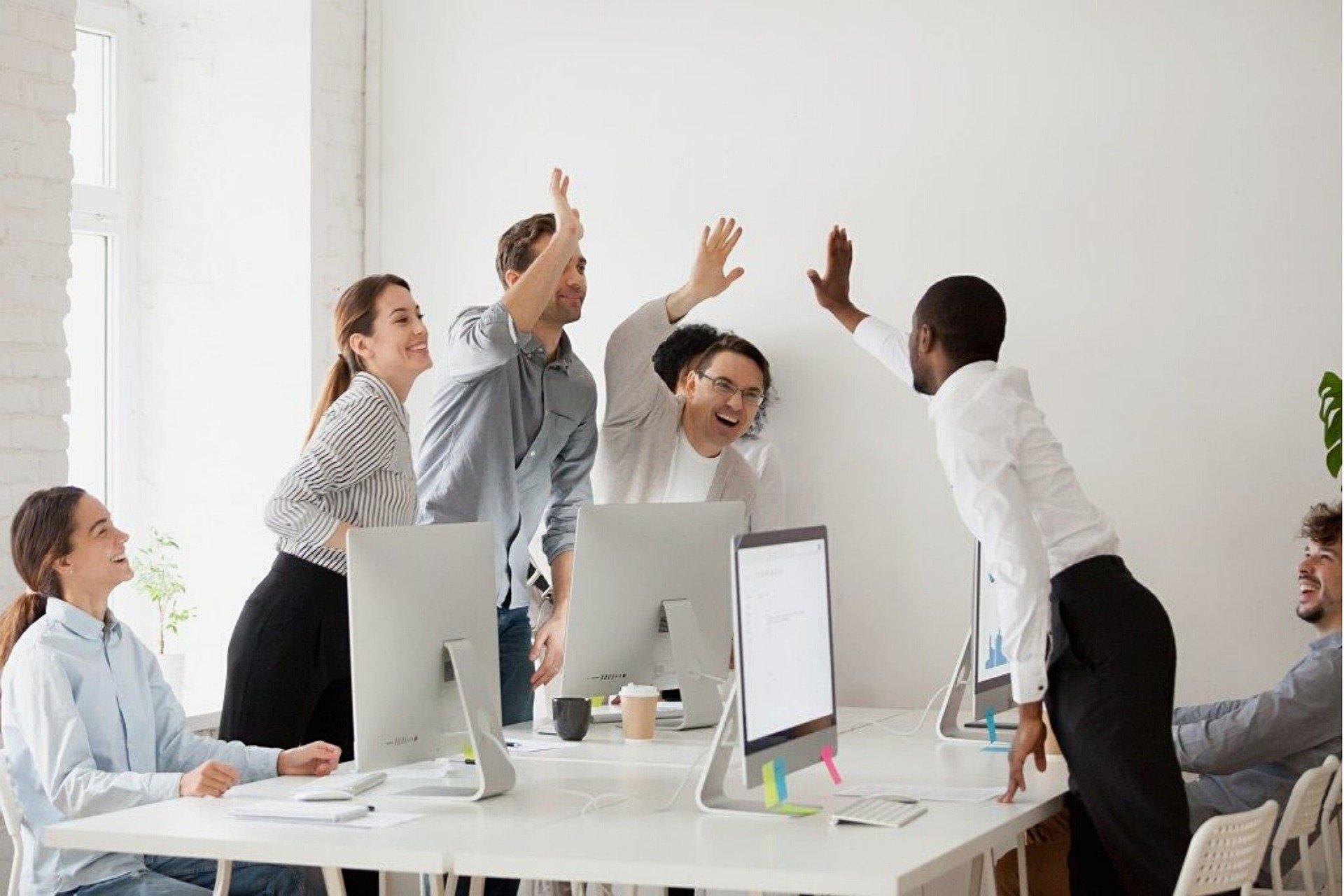 Workers high fiving conference table
